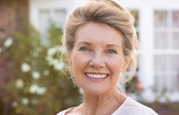 happy elderly woman after dental implants treatment showing her perfect teeth in a smile