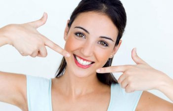 Broadly smiling young woman pointing at her beautiful teeth