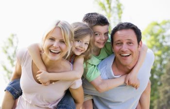 happy family of four: parents with a little boy and a girl
