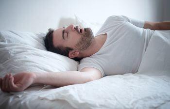 snoring man sleeping on his back