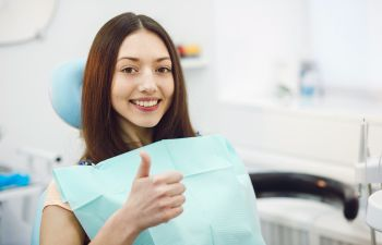 A satisfied woman showing her thumb up after dental procedure at General Dentistry in Marietta, GA.